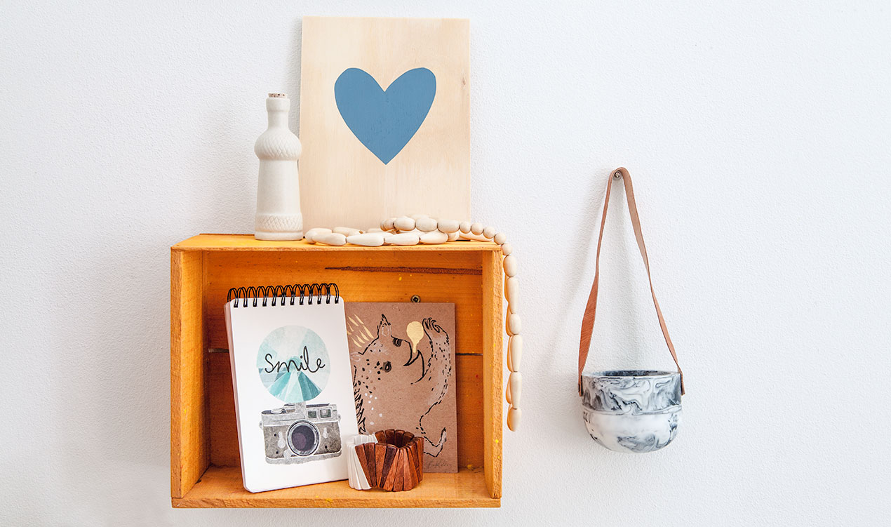 Indie styled product selection with ceramic bottle, artworks, notebook, wooden bracelet, necklace and hanging resin planter.